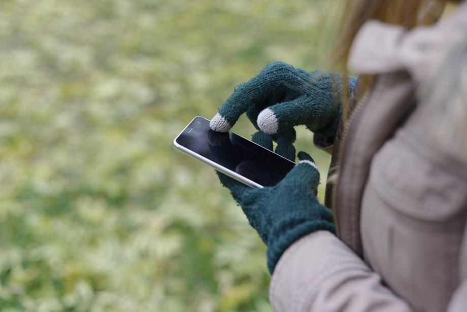 woman uses conductive gloves on smartphone
