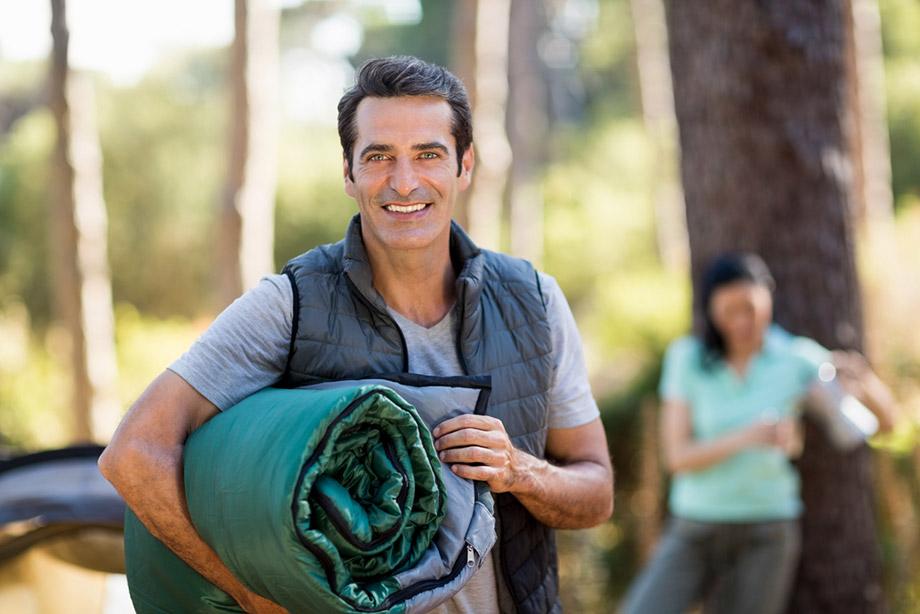 man holding sleeping bag