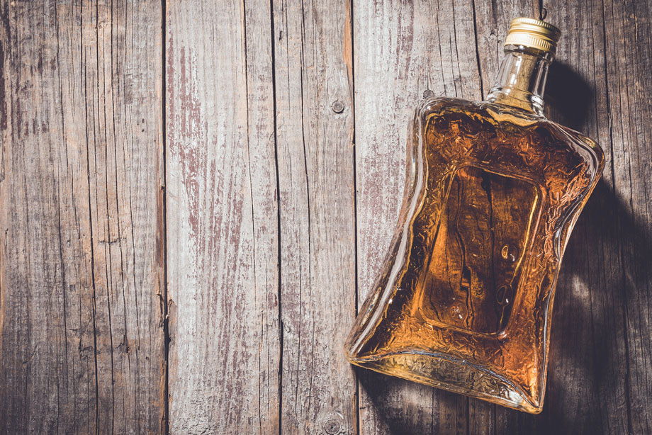 Bottle Of Alcohol On Wood Board Background
