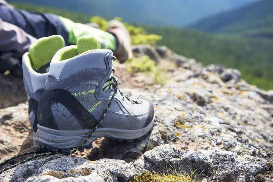 Hiking Boots Next To Person Resting On Hill