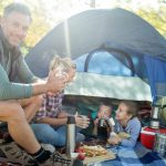 Family Together In And Around A Camping Tent