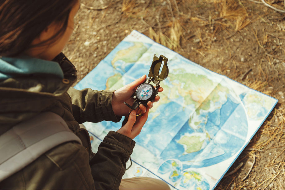 Woman Using Map And Compass