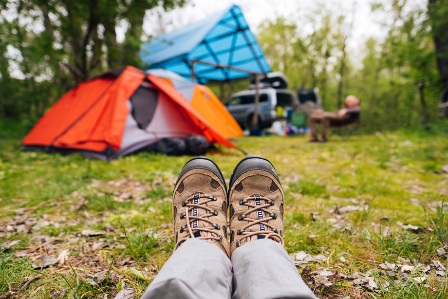 Camping Boots And Legs With Man Sitting Around Camping Site In The Background
