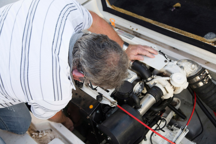 Man Inspects Boat Motor And Battery