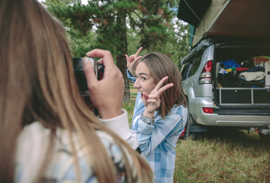 Two Girls Take A Photo In Front Of Car While Camping