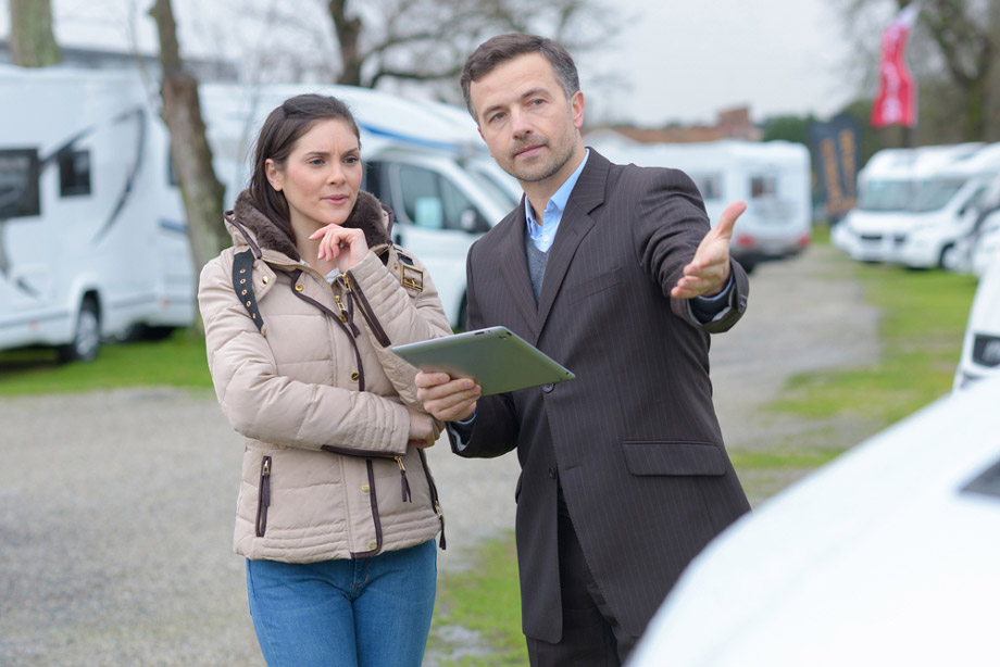 Woman Looks At Motorhome With Salesman