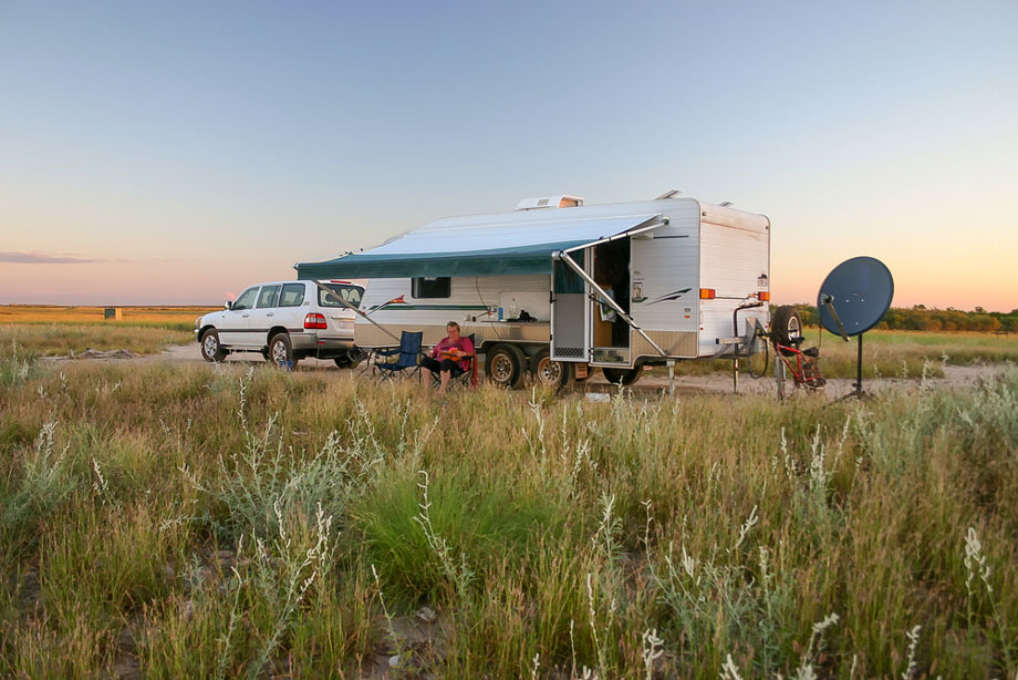 Retiree Sitting Under Awning Of Caravan With Four Wheel Drive Vehicle At Sunset