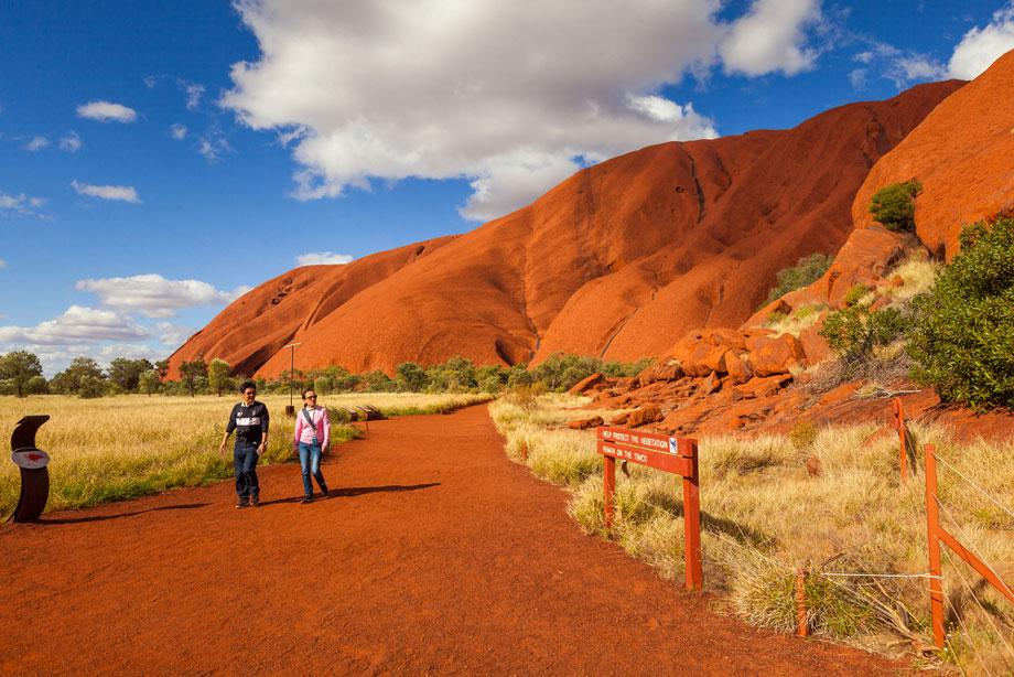 Man And Woman Walk Away From Uluru