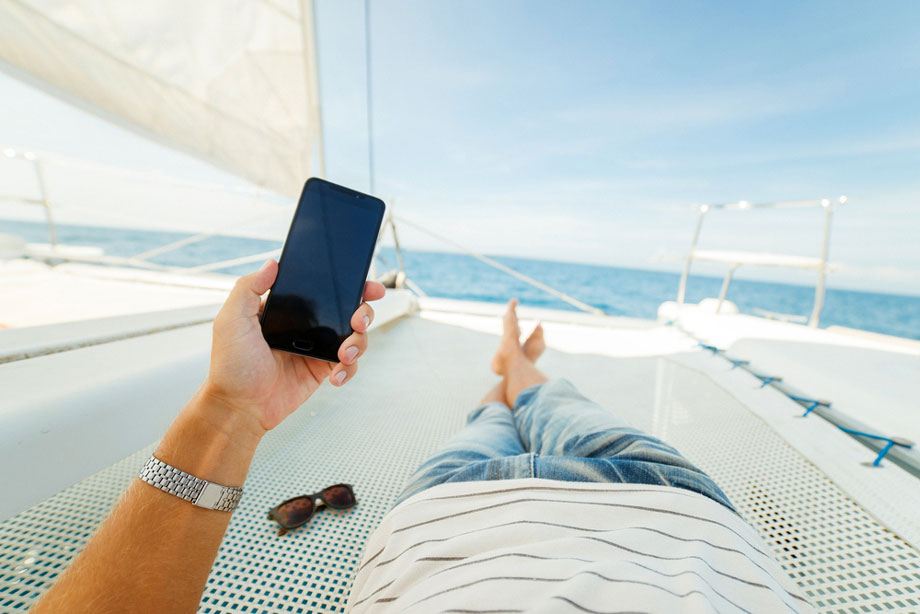 Man Looks At Phone On Boat