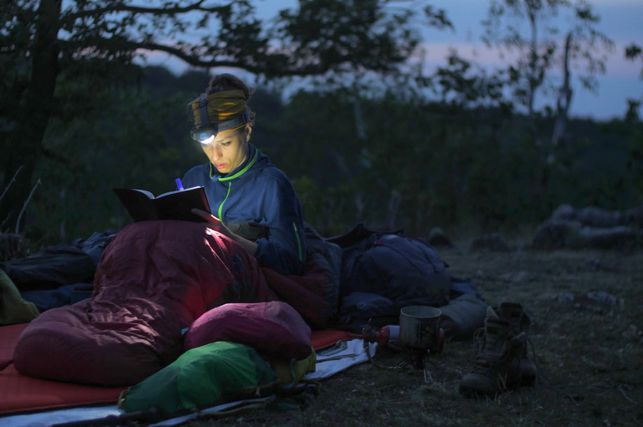 Woman In Sleeping Bag At Night Outdoors