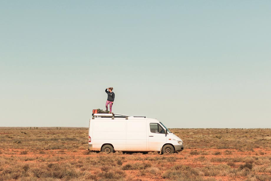 Woman Looks Around From The Top Of Her Vehicle In The Outback