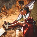 Young Man And Woman Resting In Tent While Camping
