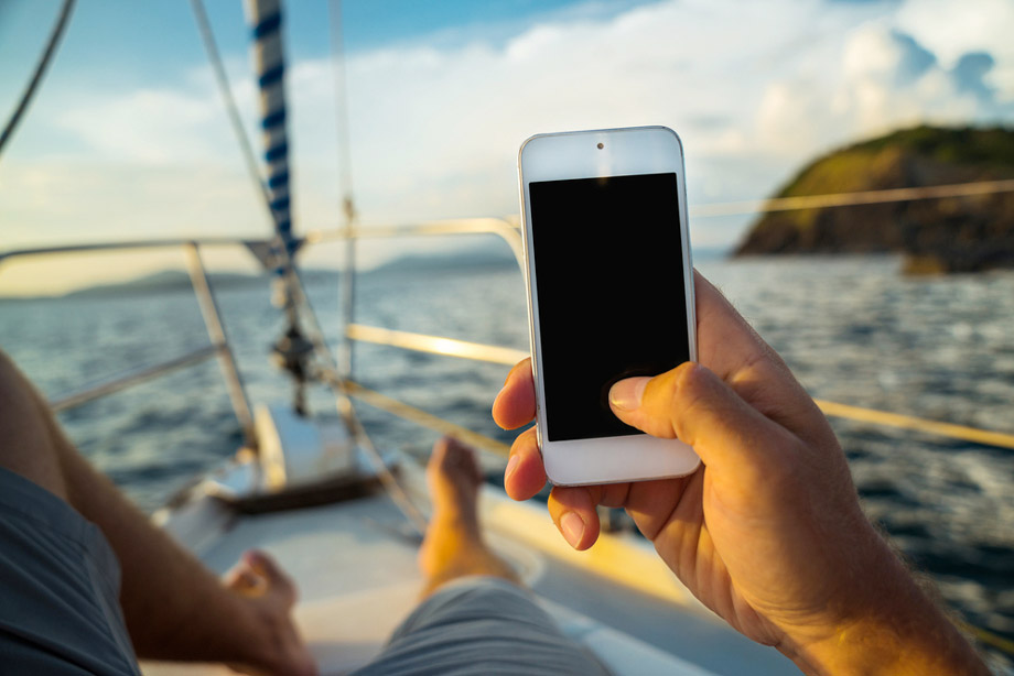 Man Uses Smartphone On A Boat