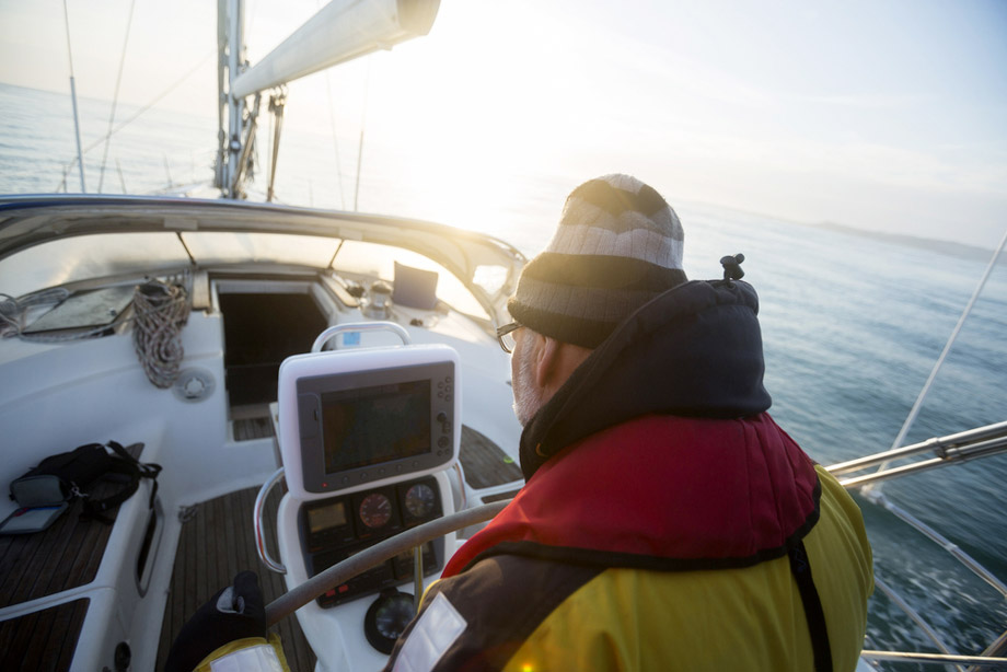 Man Using Fishfinder On A Boat