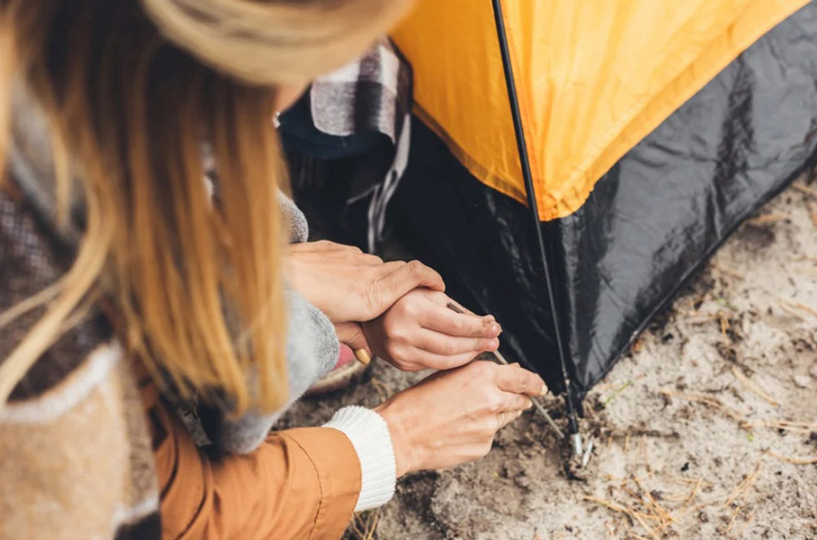 Two People Inserting Tent Peg